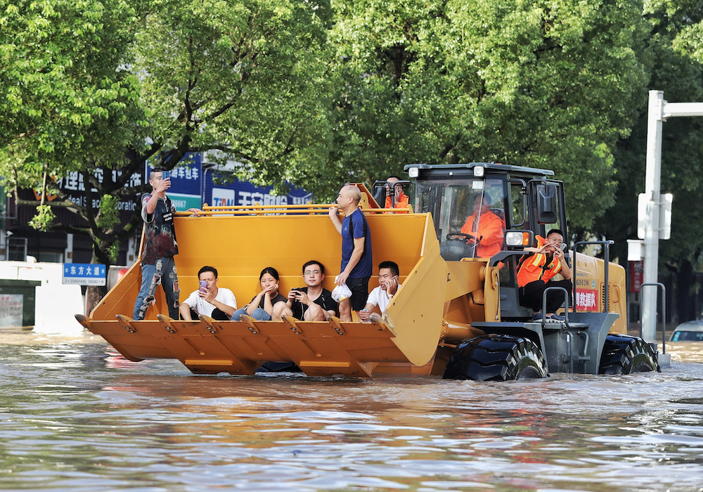 Rescue workers evacuate stranded residents with a bulldozer on a flooded street after typhoon Lekima hit Taizhou, Zhejiang province, China August 11, 2019. — Reuters pic