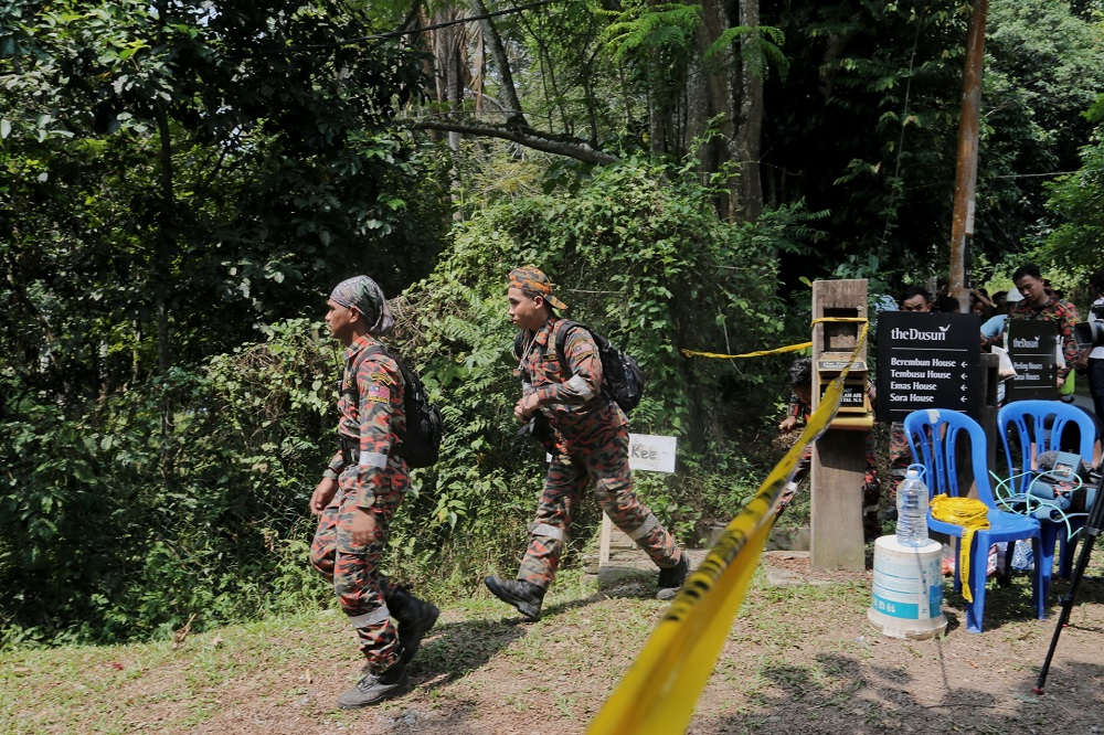 Members of the search team are seen entering an area cordoned by police after the discovery of a body in the jungle near Seremban August 13, 2019.