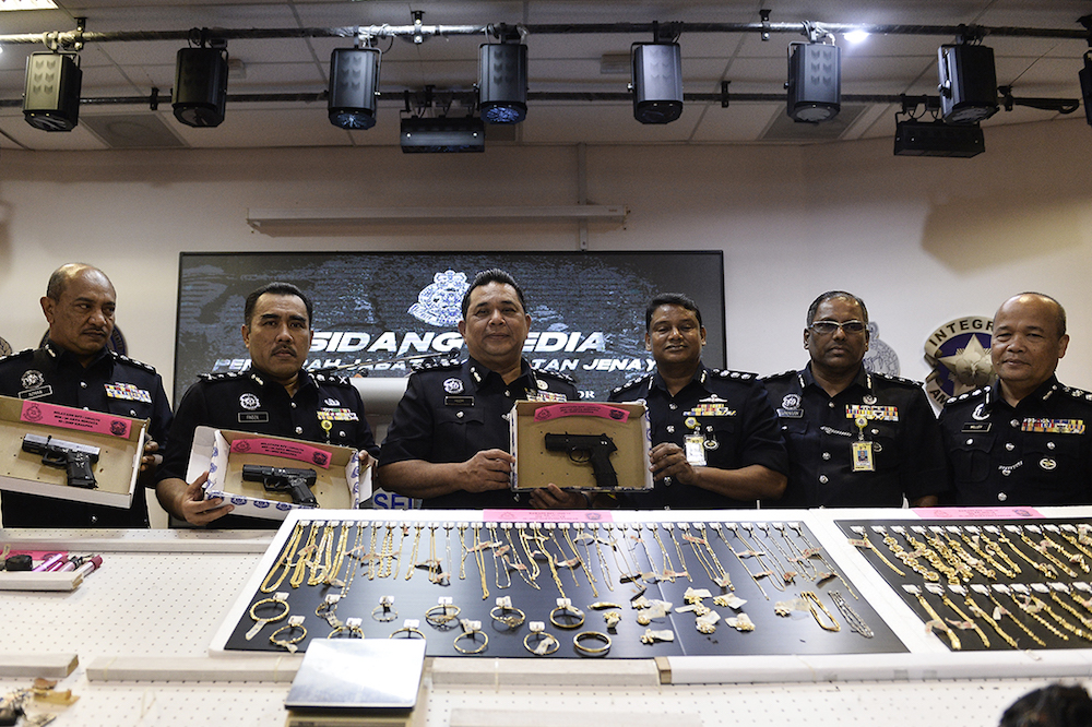 CID Director Datuk Huzir Mohamed poses for pictures with some of the seized jewellery and guns during a press conference at the Selangor Contingent Police Headquarters in Shah Alam August 15, 2019. — Picture by Miera Zulyana