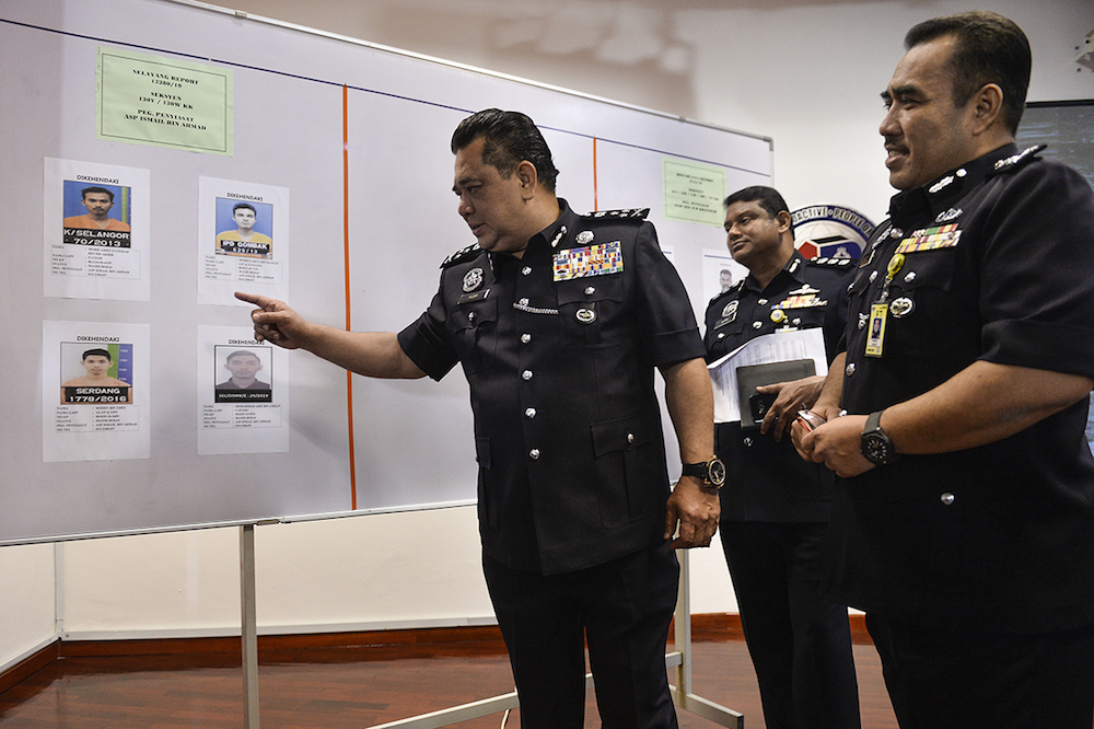 CID Director Datuk Huzir Mohamed points at the suspects' mugshots during a press conference at the Selangor Contingent Police Headquarters in Shah Alam August 15, 2019. — Picture by Miera Zulyana