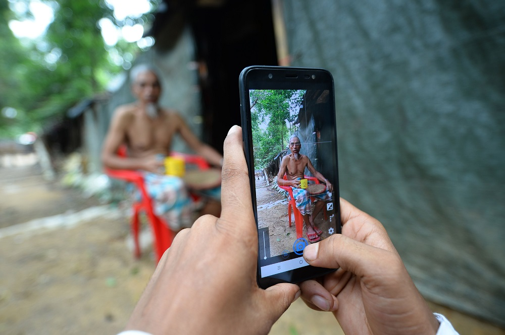 In this picture taken on July 23, 2019, Rohingya youth Mohammad Rafiq uses his mobile phone to take photos of a man by his shack at the Kutupalong refugee camp. — AFP pic