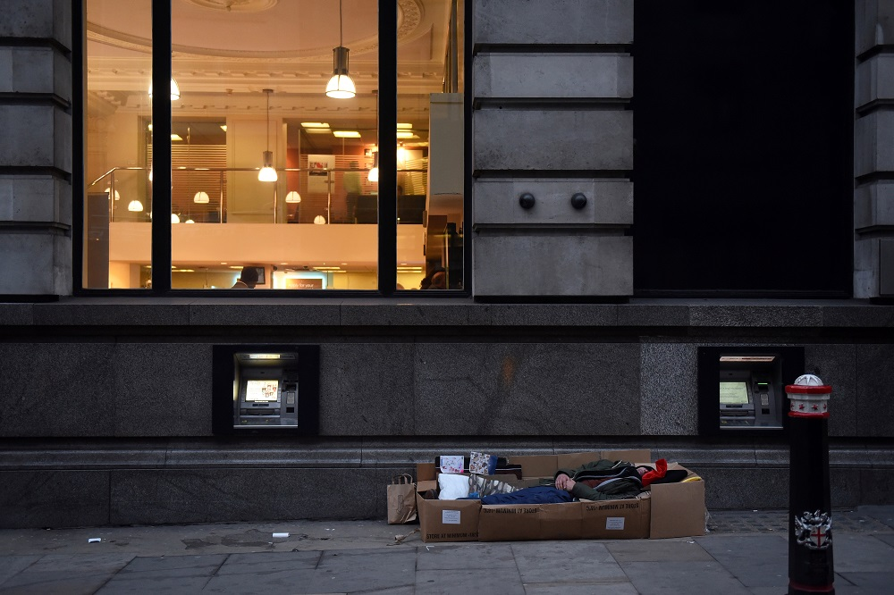 A homeless man sleeps in the cardboard box where he lives, outside Barclays Bank on Fleet Street in London December 19, 2017. — Reuters pic