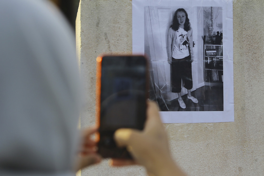 A woman takes a picture of a poster featuring missing Irish teenager Nora Anne Quoirin in Seremban August 5, 2019. — Bernama pic