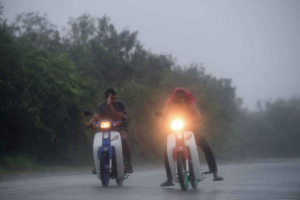 Motorcyclists battle through heavy rain and strong winds near the Kuala Kedah fishing village in Jitra August 10, 2019. — Bernama pic