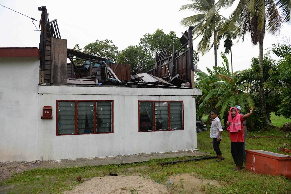 A man examines his house that was damaged in a storm in Kampung Alor Cina Tualang in Pokok Sena August 10, 2019. — Bernama pic
