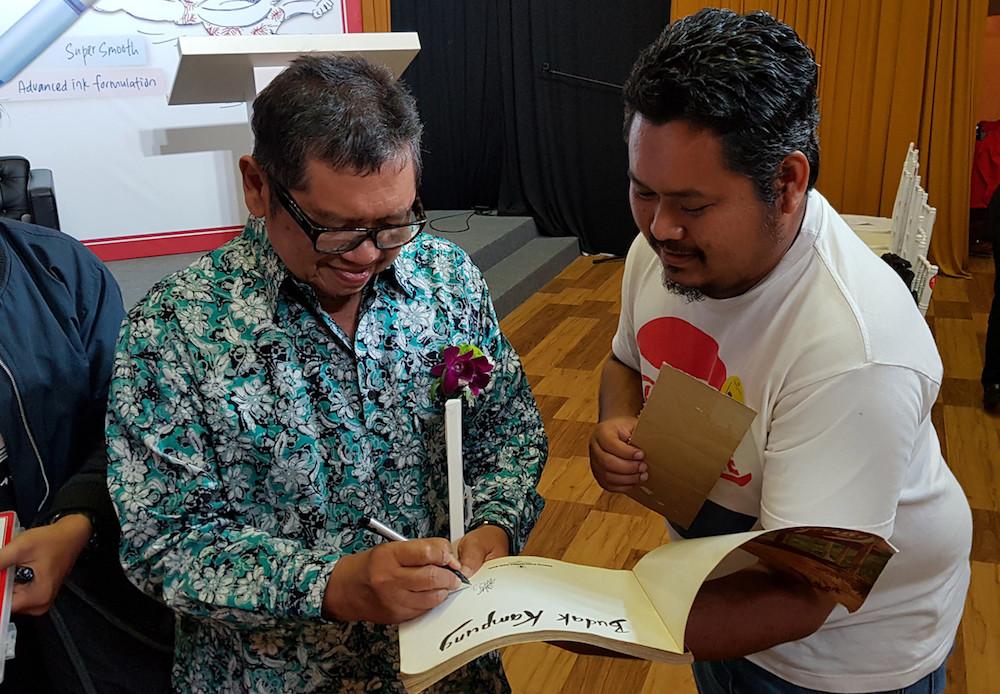Datuk Mohammad Nor Khalid, or Lat, signs a copy of his book 'Kampung Boy' at the National Art Gallery in Kuala Lumpur August 29, 2019. — Bernama pic