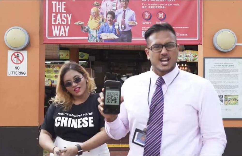 A rap video posted on Facebook by Preeti Nair (left) featuring rapper Subhas Nair (right) was directed against an e-payment advertisement (in the background). ― TODAY pic