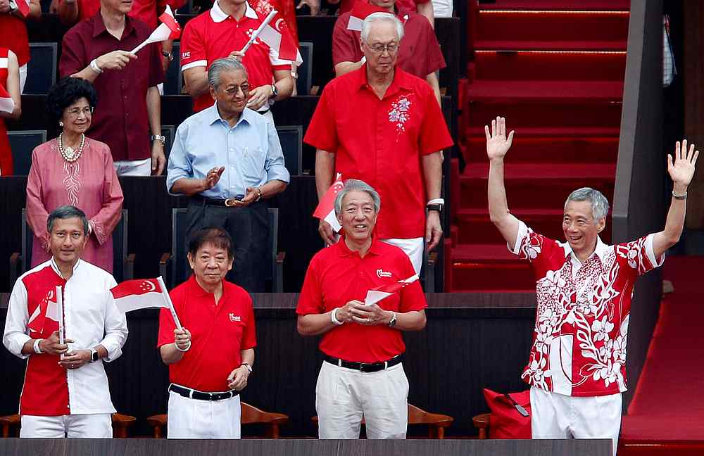 Malaysian Prime Minister Tun Dr Mahathir Mohamad and his wife Tun Dr Siti Hasmah (second row) stand for Singapore Prime Minister Lee Hsien Loong's (front right) arrival at the National Day Parade in Singapore August 9, 2019. — Reuters pic