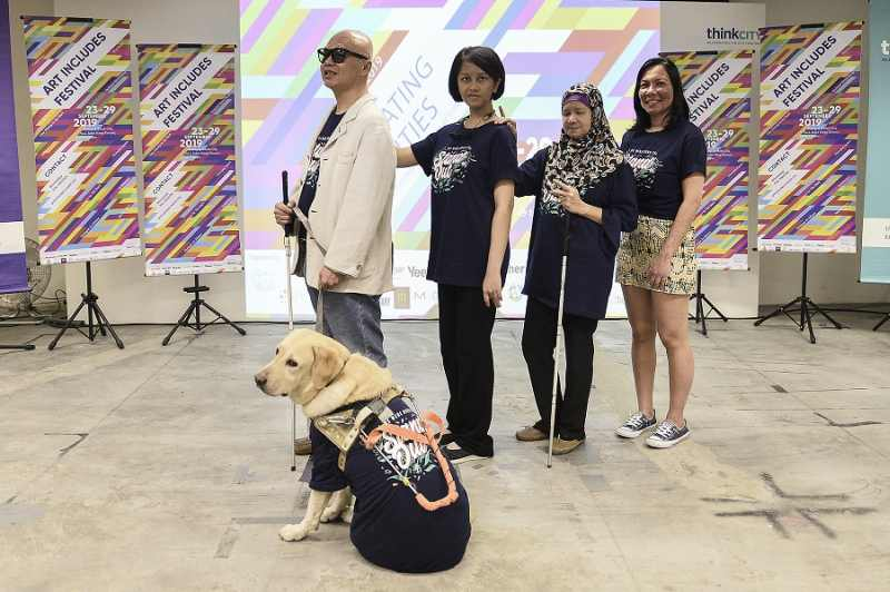 Chan and his guide dog with 'Art Includes' guest artists Wan Jamila, Jamaliah and Rozella.