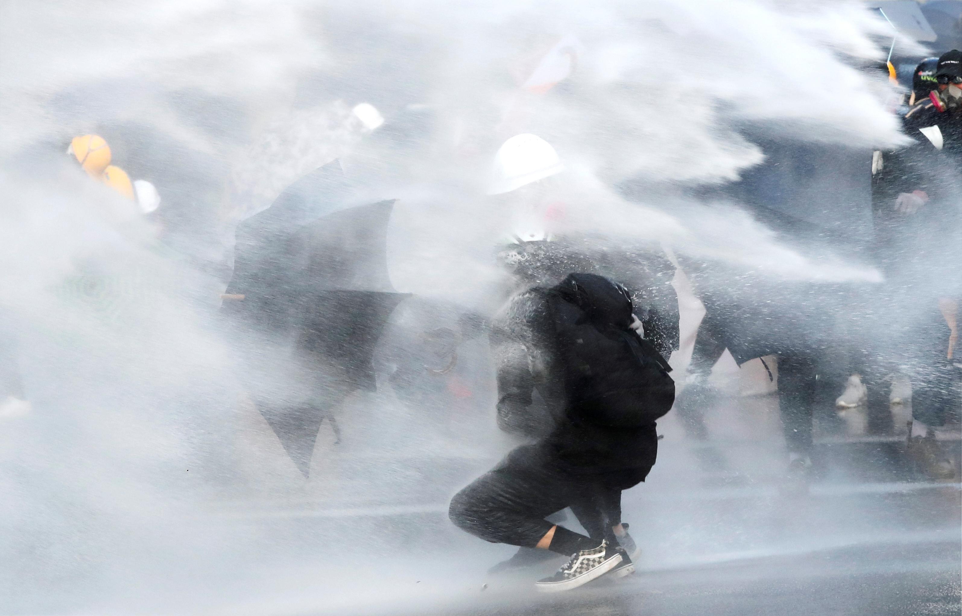 警方水炮车驶至现场,向地面及桥上发射水柱,示威者后退。-路透社-