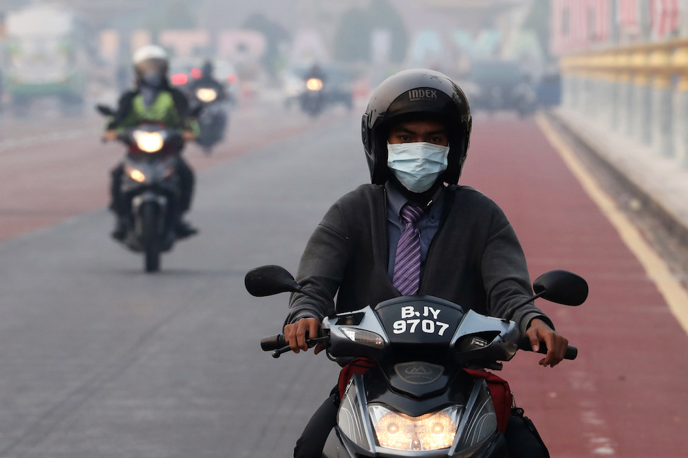 A man rides on a motorcycle in the haze in Putrajaya September 17, 2019. — Reuters pic