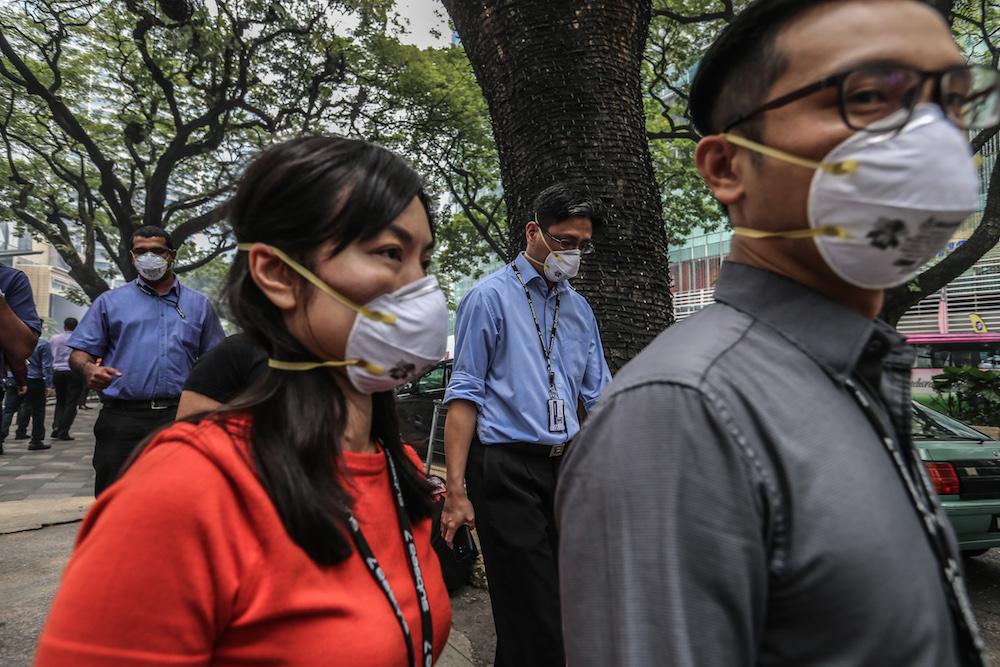 Pedestrians wear N95 masks in Kuala Lumpur September 19, 2019. — Picture by Firdaus Latif