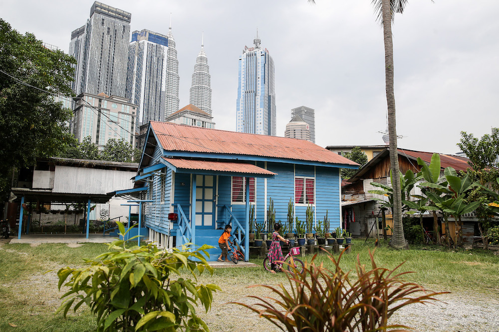 Children playing outside their house in Kampung Baru with the iconic Twin Towers looming behind them. — Picture by Yusof Mat Isa