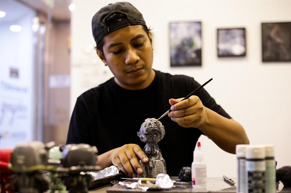 Ajim Juxta works on one of his figurines of Tun Dr Mahathir at the 'Tun M Custom Show' in Kuala Lumpur.