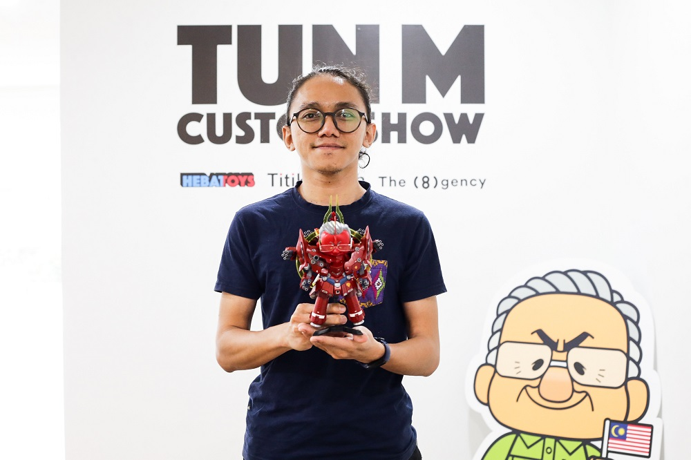 Aleff Ahmad holds up one of his artwork at the 'Tun M Custom Show' at the TitikMerah Gallery in Kuala Lumpur.
