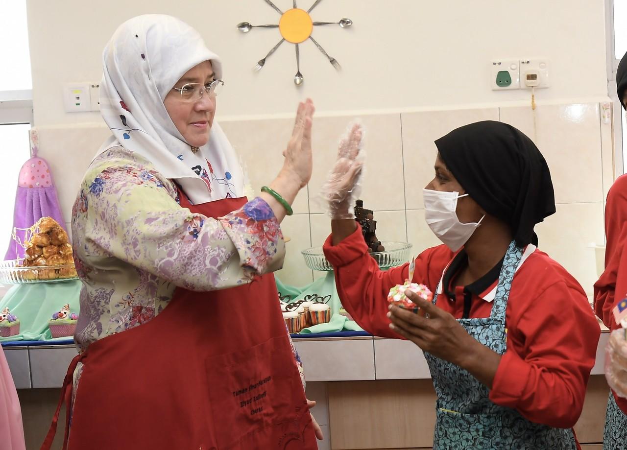 Raja Permaisuri Agong Tunku Azizah Aminah Maimunah Iskandariah high-fives a girl during a visit to Taman Sinar Harapan Ziyad Zolkefli in Cheras September 11, 2019. — Bernama pic