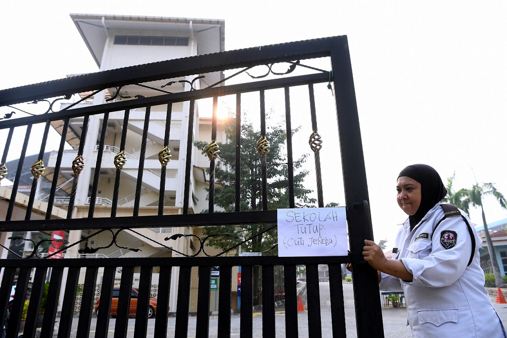 A school security guard is seen putting up a notice in front of a school in Putrajaya September 17, 2019. — Bernama pic