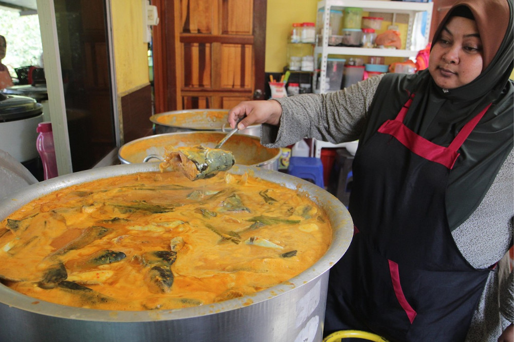 Restaurant owner Rohazlina Yusof, 43, with a pot of ikan patin gulai tempoyak at her restaurant in Kampung Bangau Tanjung, Temerloh September 21, 2019. — Bernama pic