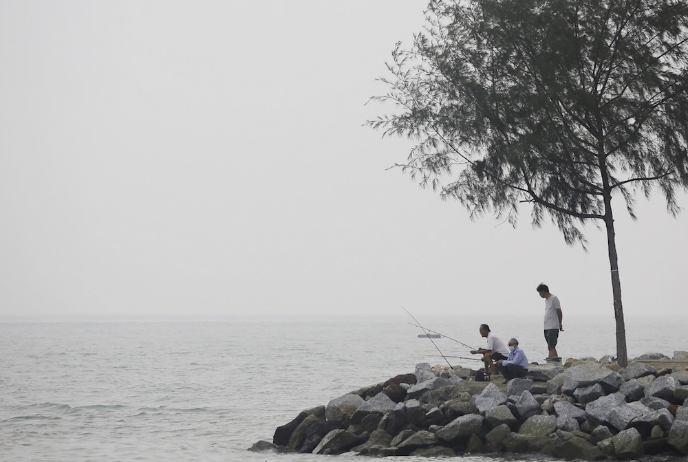 A man wears a mask as he fishes by the banks of Pantai Cahaya in Port Dickson September 21, 2019. — Bernama pic