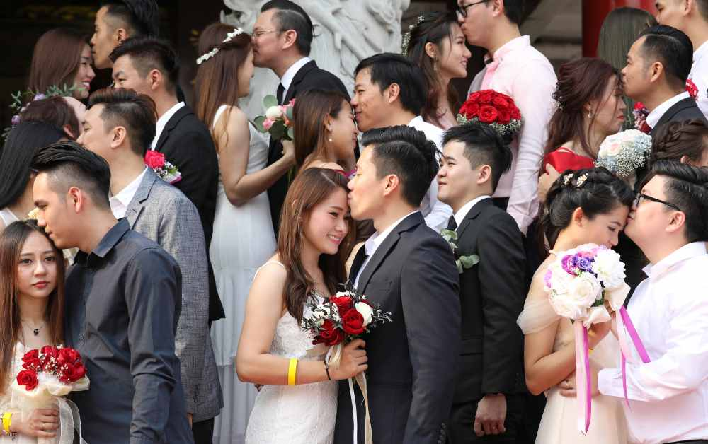 Newlywed couples kiss during a mass wedding at a Chinese temple in Kuala Lumpur September 9, 2019. ― Reuters pic