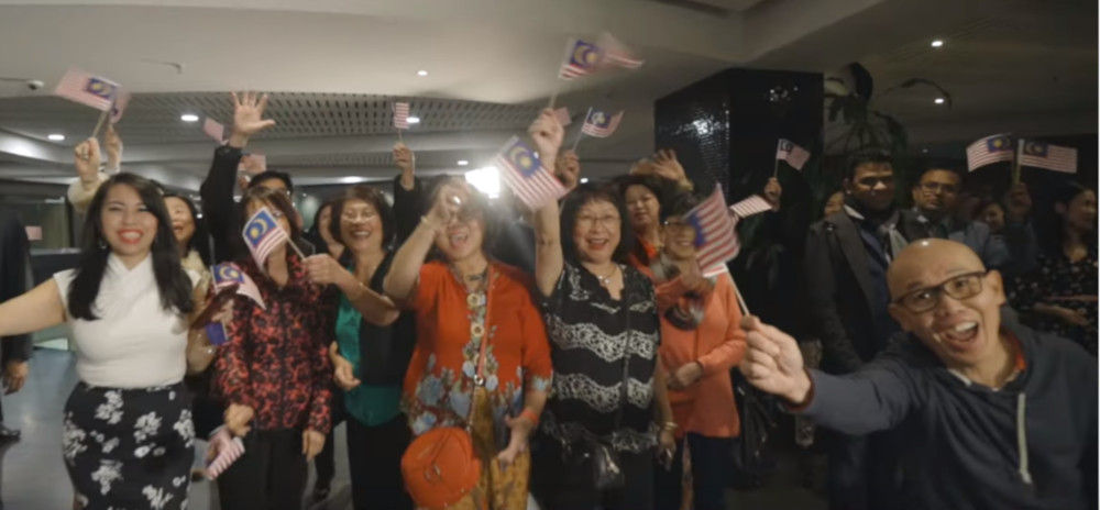 Malaysians from Melbourne waving the 'Jalur Gemilang' with pride as they sing along to 'Here in My Home'. — Screengrab via Youtube/WeTheRakyatMalaysia