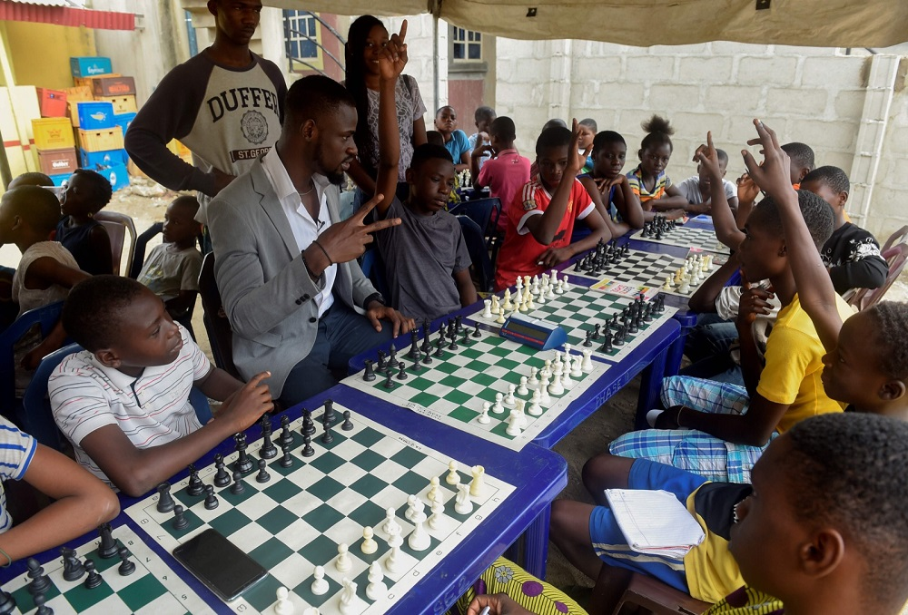 Chess consultant and player Tunde Onakoya (centre) gestures as he addresses children during a chess class at Ogolonto in Ikorodu district of Lagos August 17, 2019. — AFP pic