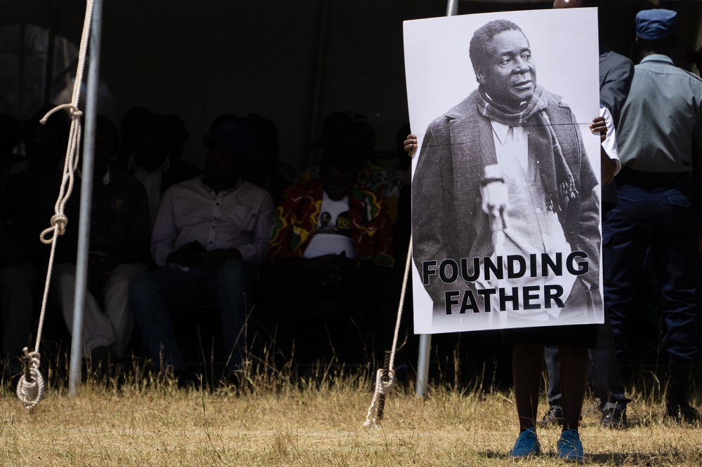 A man holds a placard reading 'Founding Father' as the coffin of late former Zimbabwean president Robert Mugabe arrives at Murombedzi Growth Point, Zimbabwe, September 16, 2019. — AFP pic
