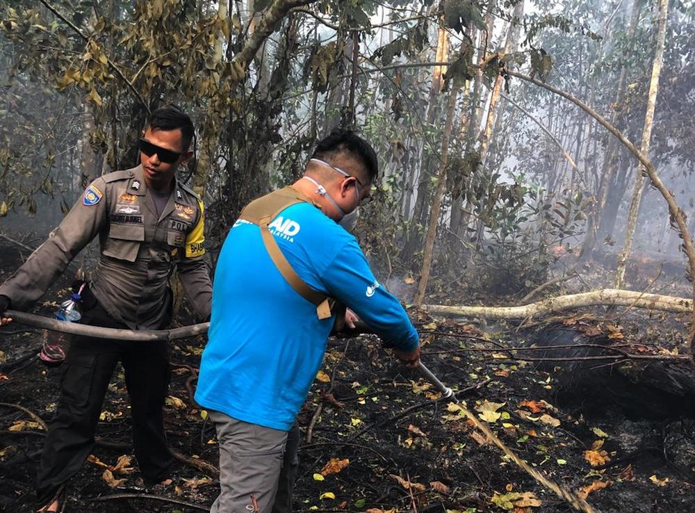 Singaporean Benjamin Tay (in blue) joined volunteer firefighters in Tanjung Sari village to help put out a peatland fire. — TODAY pic