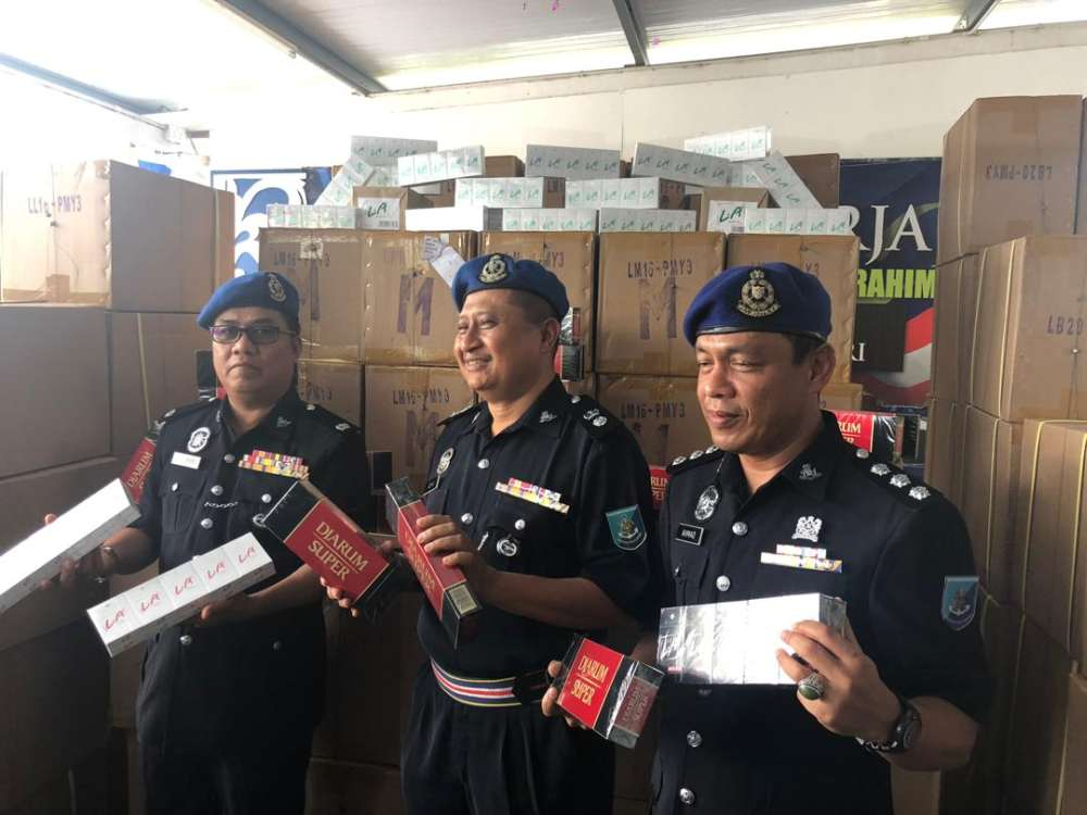 Region Two marine police deputy commander Superintendent Noor Azman Jamal (centre) with the seized contraband cigarettes at the Region Two marine police base in Tampoi, Johor Baru today. — Picture by Ben Tan