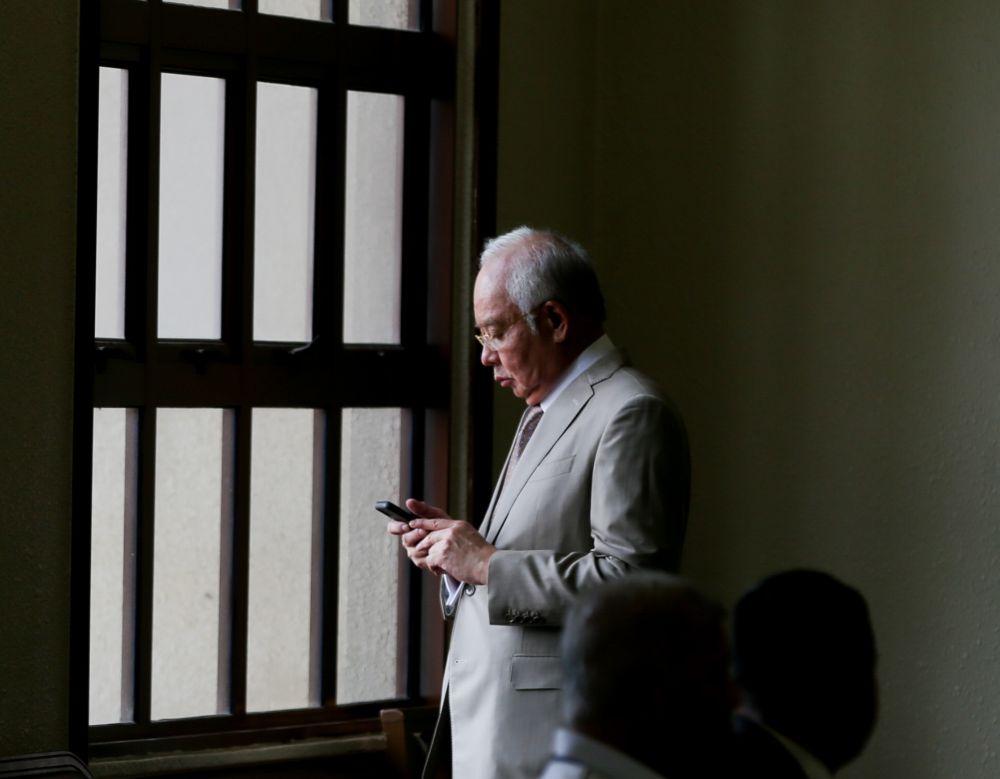 Datuk Seri Najib Razak checks his phone at the Kuala Lumpur High Court September 3, 2019.  — Picture by Firdaus Latif