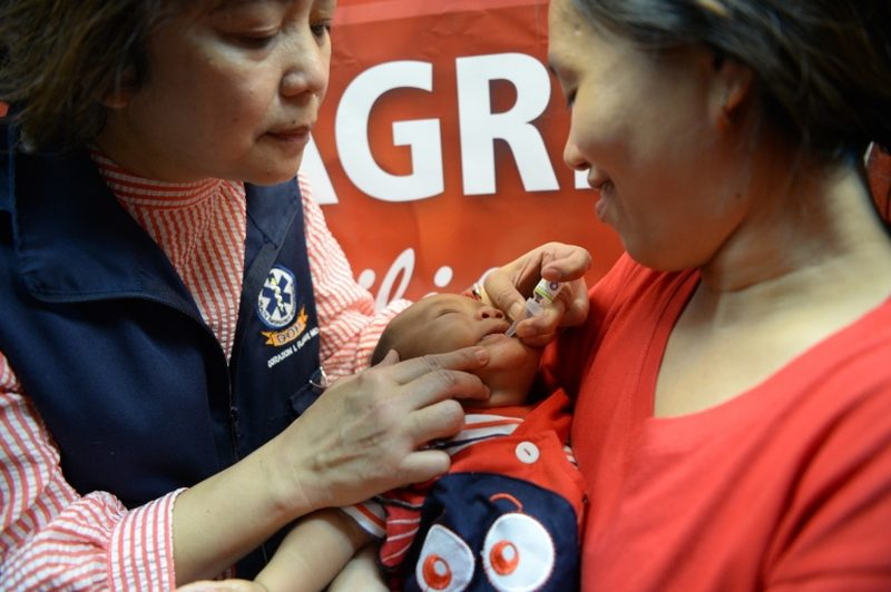 A mother watches as a health worker administers a polio vaccine in Manila. ― AFP pic