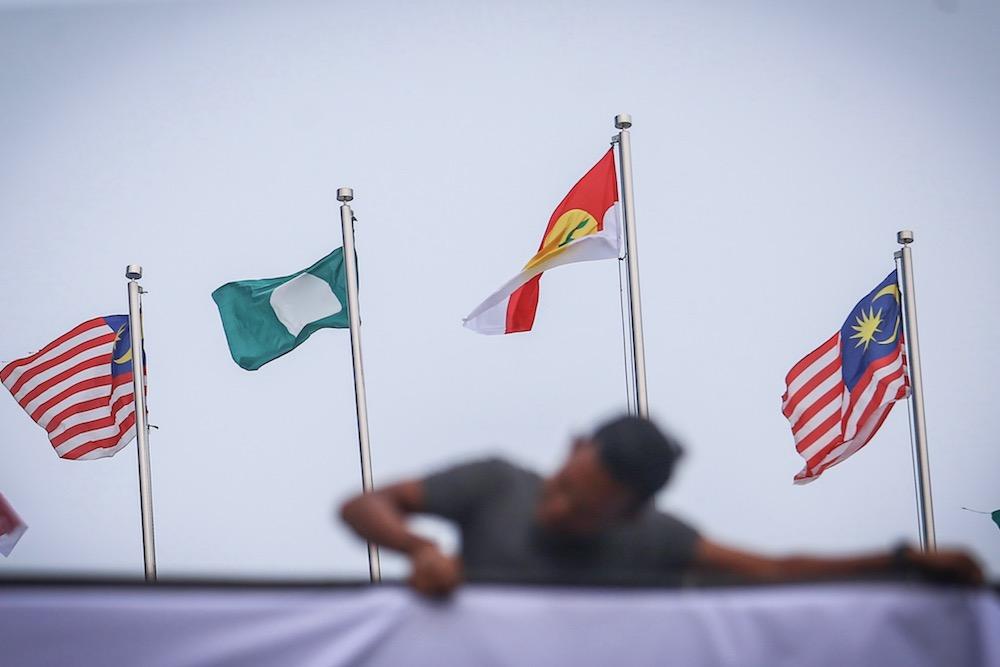 A man hangs Umno, PAS and Malaysia flags at Putra World Trade Centre in Kuala Lumpur September 12, 2019. — Picture by Hari Anggara