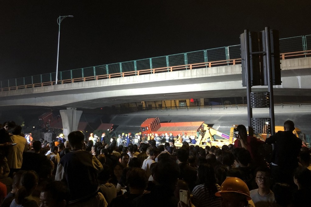 This photo shows a crowd watching workers at the site of a highway overpass collapse in Wuxi, China's eastern Jiangsu province October 10, 2019. — Picture by STR via AFP
