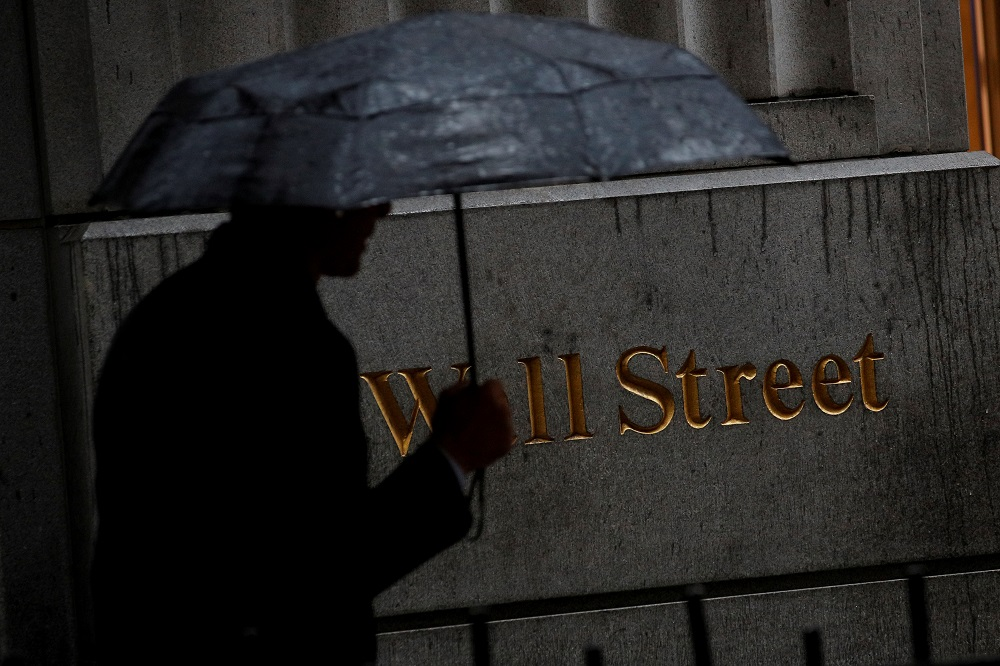 A man walks through the rain on Wall Street outside the New York Stock Exchange October 9, 2019. — Reuters pic