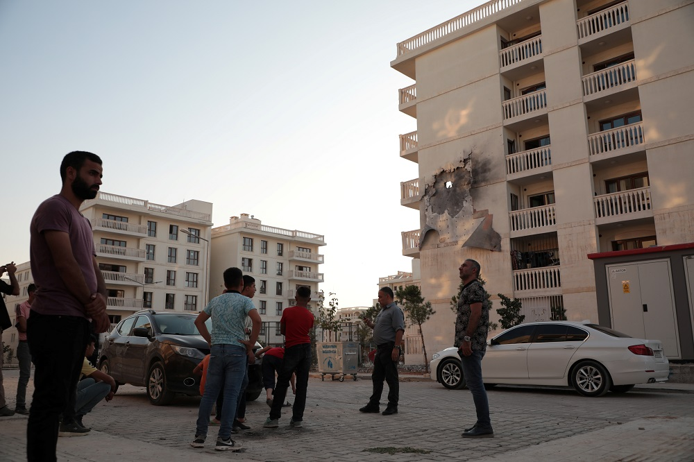 People stand in front of an apartment building which was damaged by a rocket fired from Syria, in Nusaybin, Turkey October 10, 2019. — Reuters pic