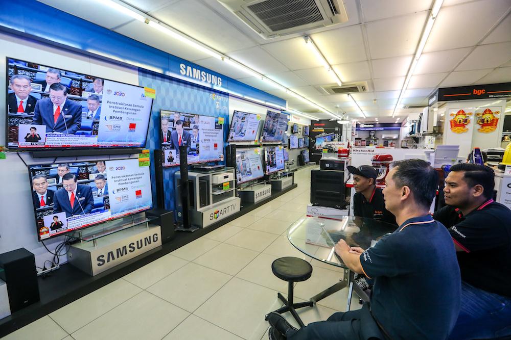 民众在吉隆坡一家电器店观看2020年财政预算案电视直播。-Firdaus Latif-
