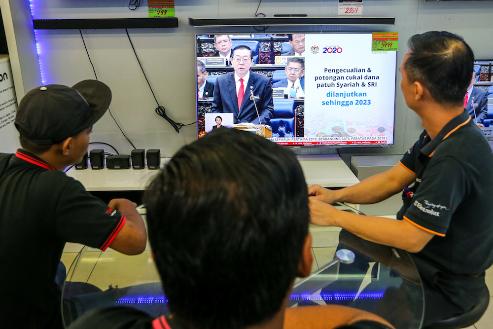 People watch a 'live' telecast of the tabling of Budget 2020 by Finance Minister Lim Guan Eng at an electronics shop in Kuala Lumpur October 11, 2019. — Picture by Firdaus Latif