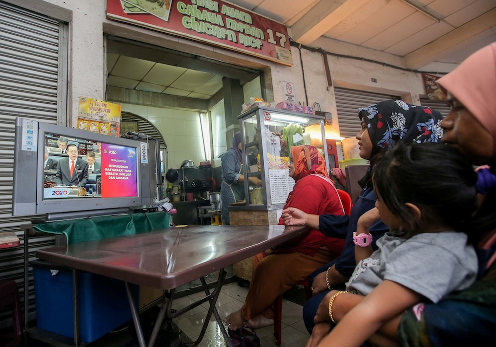 People watch the Budget 2020 speech by Finance Minister Lim Guan Eng 'live' at a restaurant in Medan Selera Medan Kidd in Ipoh October 11, 2019. — Picture by Farhan Najib