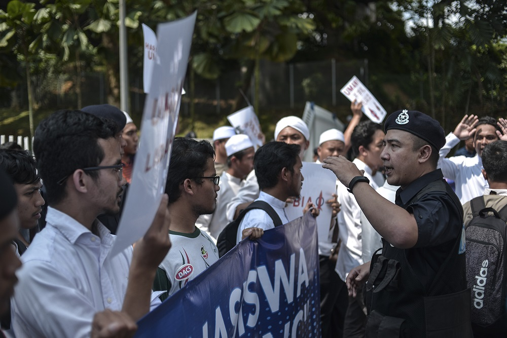 A police officer speaks to the students in front of Universiti Malaya in Kuala Lumpur October 25, 2019. — Picture by Shafwan Zaidon