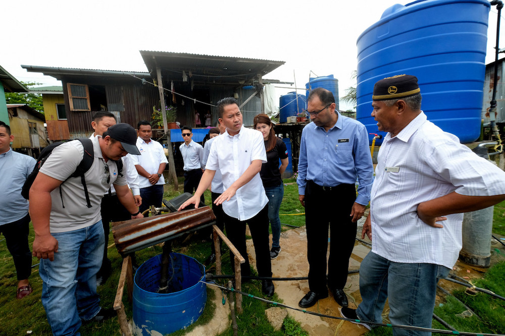 Sabah Water Department director Amarjit Singh (2nd right) looks on as Sabah Infrastructure Development Minister Datuk Peter Anthony (centre) examines a well in Kampung Pulau Berhala, Sandakan October 2, 2019. — Bernama pic