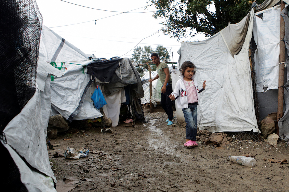 A girl makes her way next to tents at a makeshift camp for refugees and migrants next to the Moria camp, following a rainfall on the island of Lesbos, Greece, October 8, 2019. — Reuters pic