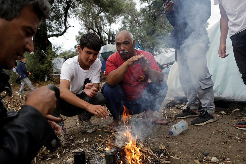 Men warm themselves next to a fire at a makeshift camp for refugees and migrants next to the Moria camp, following a rainfall on the island of Lesbos, Greece, October 8, 2019. — Reuters pic