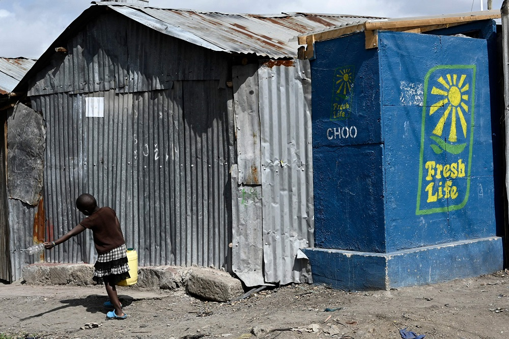 A young girl carrying a jerrican of water walks past 'Fresh Life' toilets, installed by Sanetary in the Mukuru slums in Nairobi August 8, 2019. — AFP pic