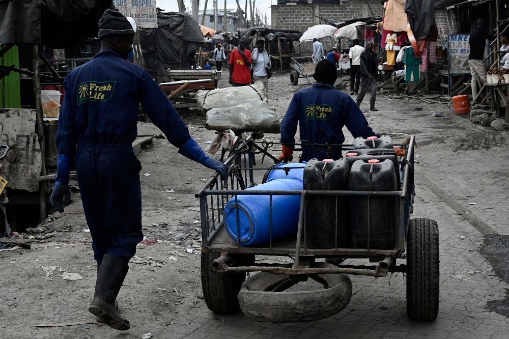 Sanergy workers walk with a trailer with used cartridges from portable latrines that were removed by Sanergy staff in the Mukuru slums in Nairobi August 8, 2019. — AFP pic