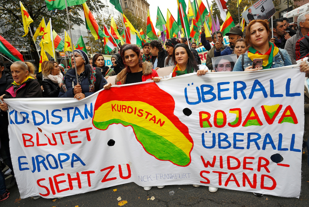 People carry a banner reading 'Kurdistan it's bleeding, Europe is just watching' during a pro-Kurdish demonstration against Turkey's military action in northeastern Syria in Frankfurt, Germany, October 19, 2019. — Reuters pic