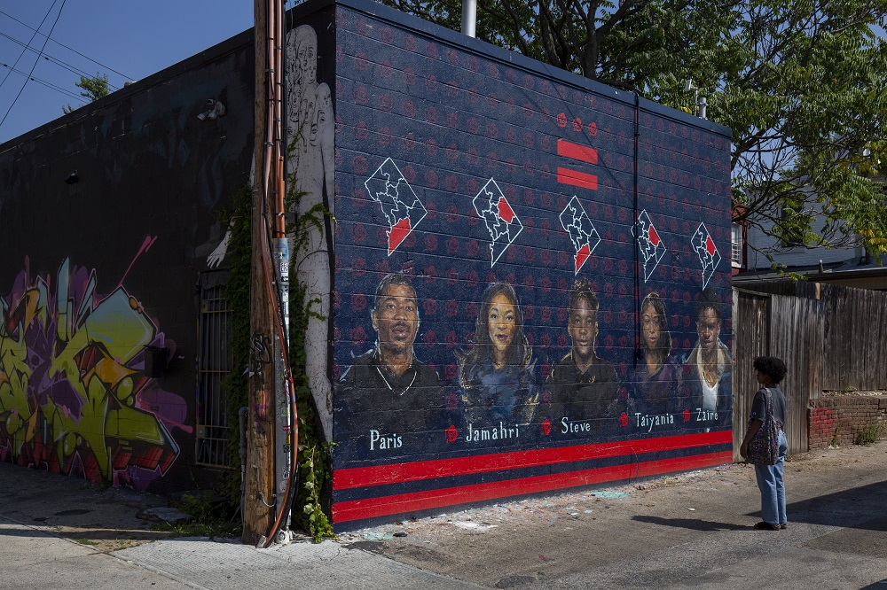 Lauryn Renford, 17, looks at a mural by Martin Swift depicting teenage gun violence victims including Zaire Kelly (right), Renford's boyfriend who was shot dead in 2017, in Washington September 11, 2019. — AFP pic