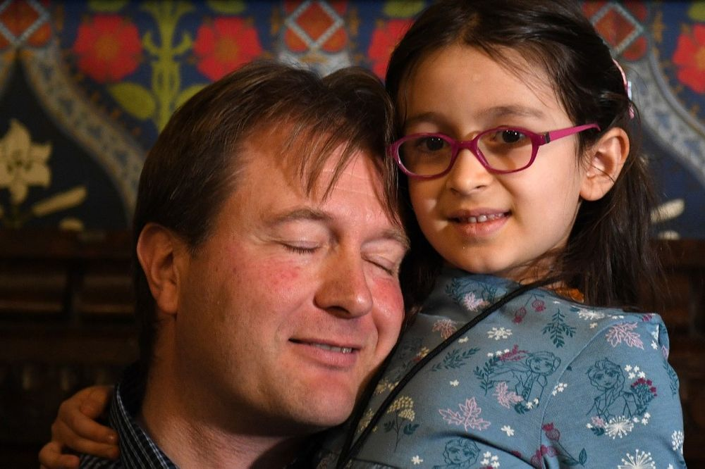 Richard Ratcliffe, husband of British-Iranian aid worker Nazanin Zaghari-Ratcliffe jailed in Tehran since 2016, holds his daughter Gabriella during a news conference in London, on October 11, 2019. — AFP pic