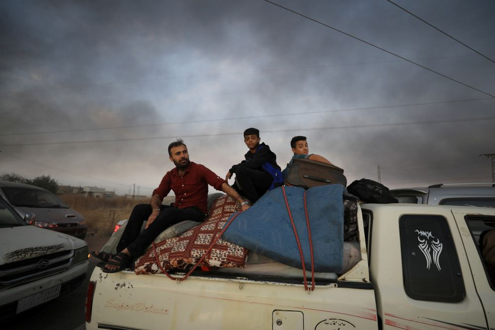 People sit on belongings at a back of a truck as they flee Ras al Ain town, Syria October 9, 2019. ― Reuters pic