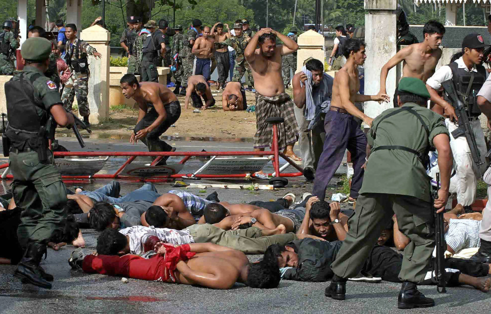 In this file photo taken October 25, 2004, police and soldiers arrest demonstrators at Tak Bai police station in Thailand's southern province of Narathiwat. — AFP pic