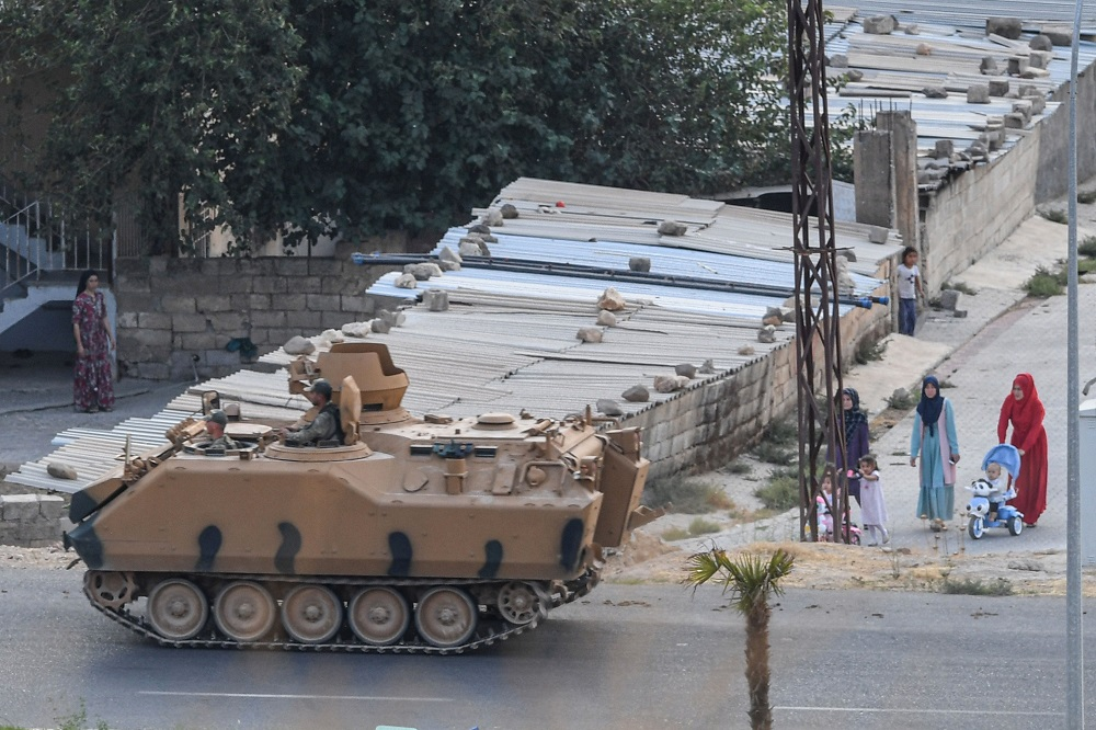 This picture taken on October 17, 2019 from the Turkish side of the border with Syria in the Ceylanpinar district city of Sanliurfa shows Turkish army soldiers manning an armoured vehicle as women and children pass by near the Syrian town of Ras al-Ain during the Turkish offensive against Kurdish groups in northeastern Syria. — AFP pic